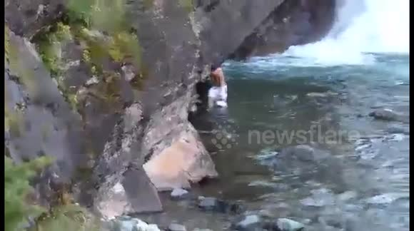 Man saves coyote after it fell off a waterfall into cold water