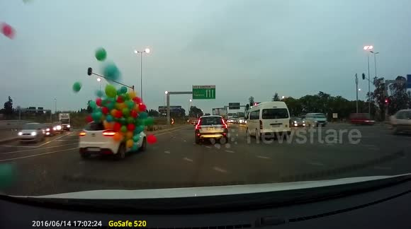 Dozens of balloons fly off car on busy road