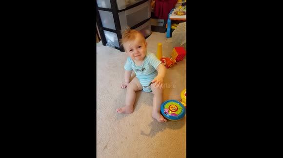 Baby cries as a piece of vinyl gets stuck to his fingers