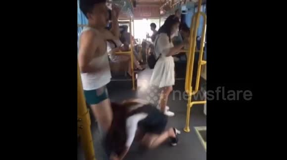 Woman pulls off man's shorts as she falls on bus
