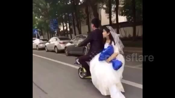 Groom doesn't notice his bride fall off the back of their wedding scooter