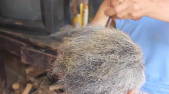 Chinese barber practising rare art to cut hair with hot tongs