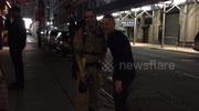 People take pictures with man dressed as a Ghostbuster