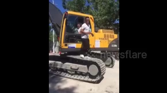 Man uses moving digger tracks as a treadmill to work out