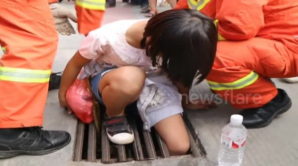 Firefighters rescue a girl with leg stuck in manhole cover