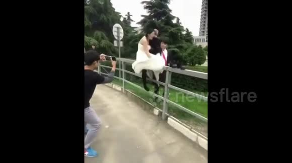 Bride and groom fall over during wedding photoshoot